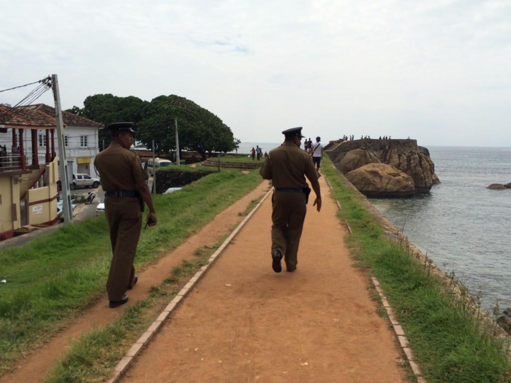 Hvor end man næsten færdes på Sri Lanka møder man altid betjente med tjeneste pistoler. Altid patroljerende 2 og 2. Her på fæstningsmuren, man kan følgende rundt langs vandet. Galle Fort.